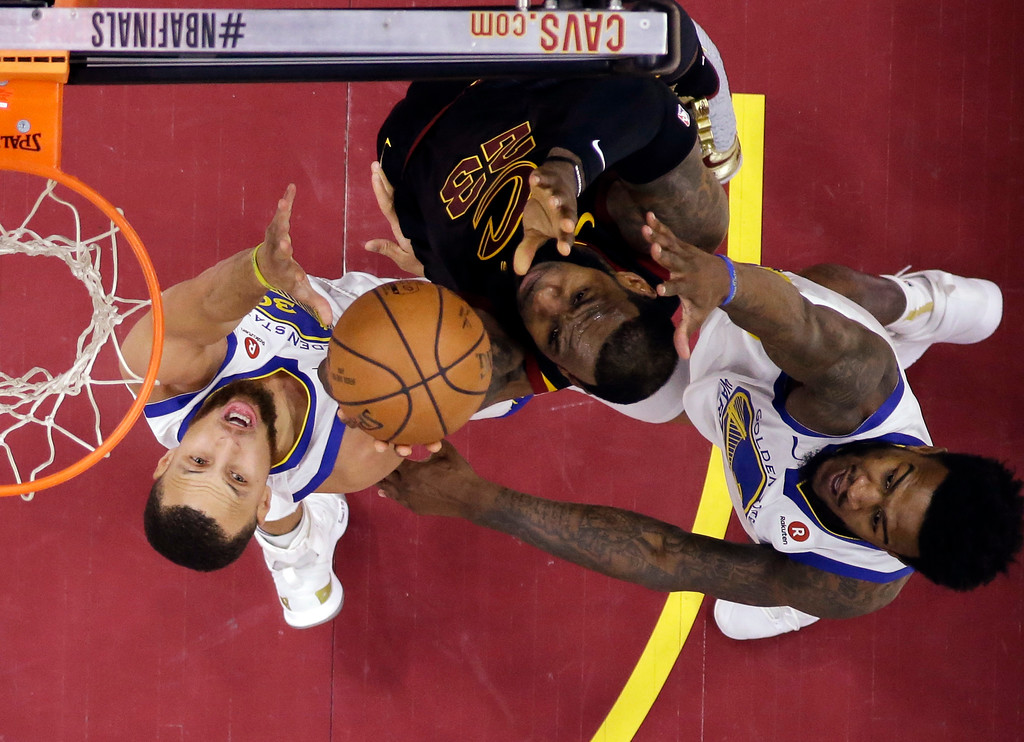 . Cleveland Cavaliers\' LeBron James (23) vies for a rebound against Golden State Warriors\' Stephen Curry, left, and Jordan Bell during the first half of Game 3 of basketball\'s NBA Finals, Wednesday, June 6, 2018, in Cleveland. (AP Photo/Carlos Osorio, Pool)