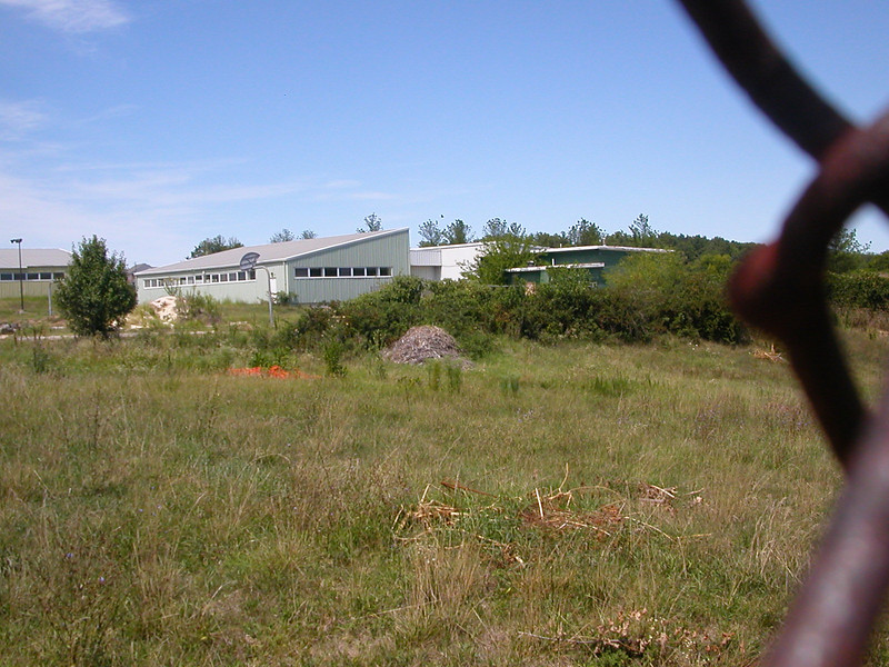Another view of the assembly and service Building (dark Green) through a fence