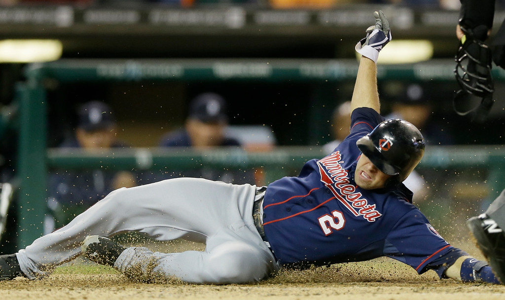 . Minnesota Twins\' Brian Dozier safely scores from second on a two-run single by teammate Eric Fryer during the fifth inning of a baseball game against the Detroit Tigers in Detroit, Saturday, Sept. 27, 2014. (AP Photo/Carlos Osorio)