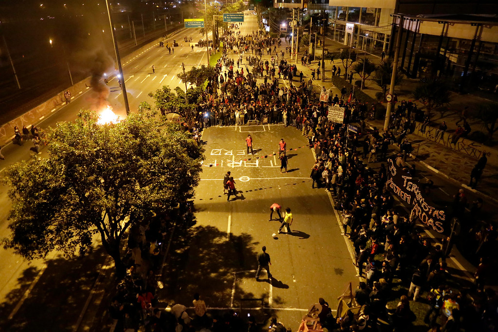 . Protesters play on a makeshift soccer pitch after blocking a main thoroughfare during a march in Sao Paulo, Brazil, Thursday, June 19, 2014. Protesters smashed the windows of luxury cars inside a dealership, trashed banks and fired powerful fireworks at police during a demonstration that drew about 2,000 Thursday as Sao Paulo, Brazilís biggest city, hosted a World Cup match. (AP Photo/Nelson Antoine)