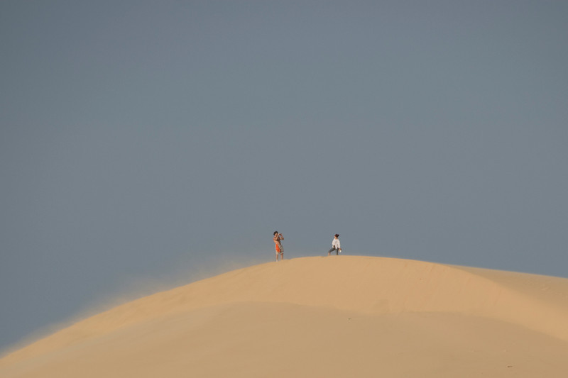 Tourists taking photos at the white sand dunes - Mui Ne, Vietnam