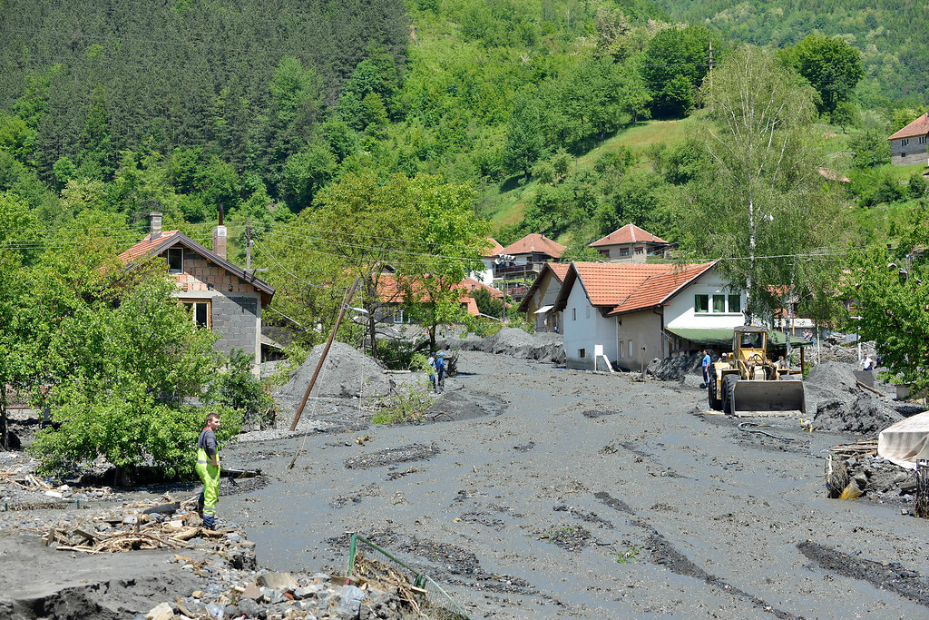 . Heavy machinery is used to clean streets in the village of Topcic Polje, that was damaged by a landslide, near the Bosnian town of Zenica, 90 kilometers north of Sarajevo, on Monday May 19, 2014. At least 35 people have died in Serbia and Bosnia in the five days of flooding caused by unprecedented torrential rain, laying waste to entire towns and villages and sending tens of thousands of people out of their homes, authorities said. (AP Photo/Sulejman Omerbasic)