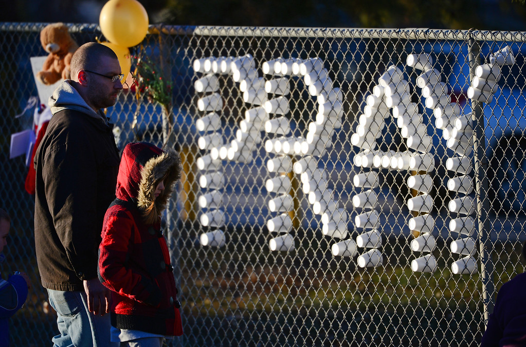 . Friends and students take a moment to pray at a tribute for shooting victim Claire Davis set up along Dry Creek road near Arapahoe High School in Centennial, CO on December 15, 2013. Students from the high school attended a prayer service to pray for the recovery of Davis who was shot during the recent shooting at the high school.  (Photo By Helen H. Richardson/ The Denver Post)