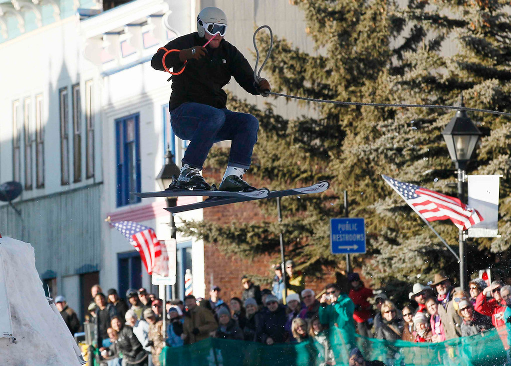 . A skier, who is pulled by a horse, flies off a jump in the snow-covered main street during the annual skijoring race in downtown Leadville, Colorado March 2, 2013. This was the 62nd year for the competition in Leadville. REUTERS/Rick Wilking