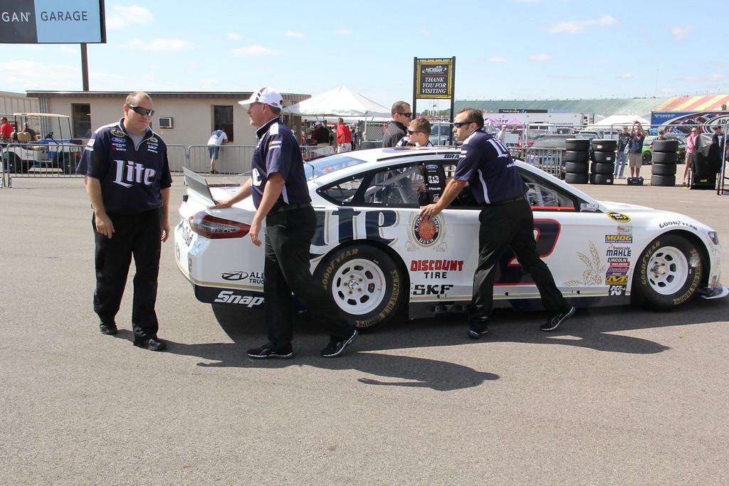 . Crew members push Brad Keselowski\'s car into its garage stall.