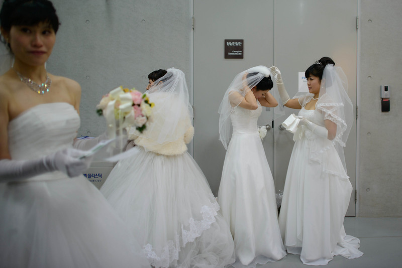 ". Brides prepare for a mass wedding at an event held by the Unification Church in Gapyeong on February 12, 2014. Unification Church members forming 2500 couples from 52 countries were married in a mass wedding in South Korea -- only the second such event since the death of their ""messiah\"" and controversial church founder Sun Myung Moon. (ED JONES/AFP/Getty Images)"