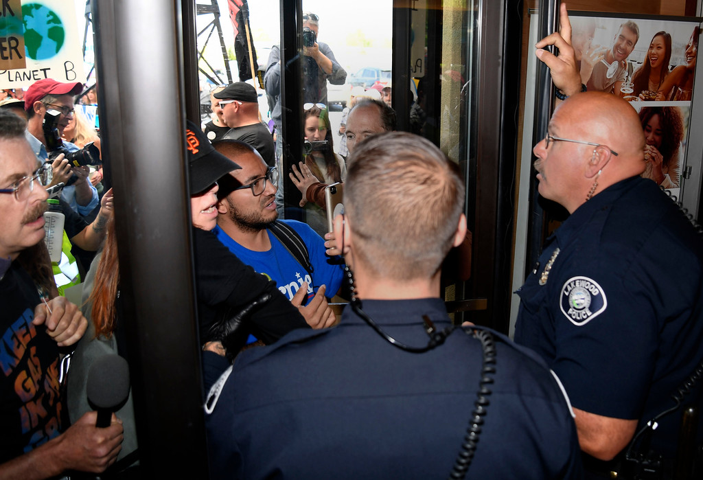. LAKEWOOD, CO - MAY 12: Colorado community, climate and fracking activists rush inside the lobby to the Holiday Inn as Lakewood PD tries to maintain order as the group protests a Bureau of Land Management oil and gas lease auction May 12, 2016 in Lakewood. The group rallied to disrupt the auction which was being held inside the hotel. The groups plan was to demand that public lands be no longer drilled, mined, or fracked. The protest was part of a global week of action focused on citizen action to keep fossil fuels in the ground and promote clean renewable energy, and comes days after the Colorado Supreme Court denied local authority to regulate fracking. (Photo By John Leyba/The Denver Post)