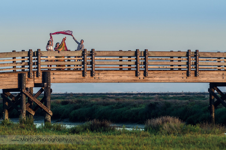 Indian family under red veil on the wood bridge at Don Edwards Refuge in Fremont