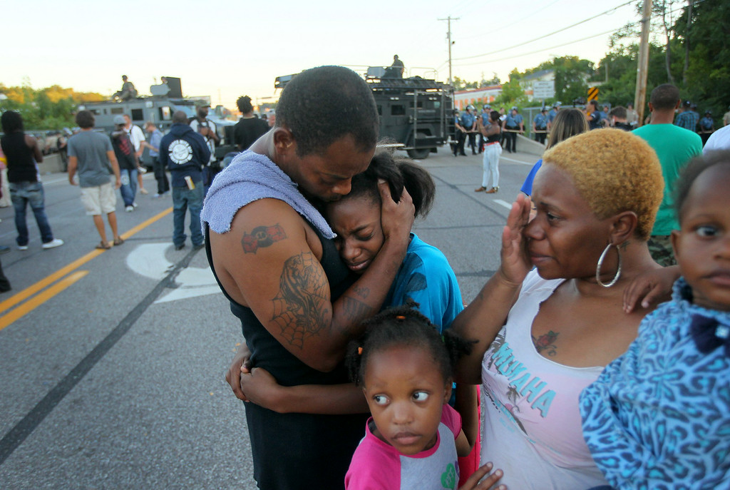 . Terrell Williams El hugs his daughter Sharell, 9, while standing with his wife, Shamika Williams, and daughters Tamika, 6, and Sharell, 2, on Wednesday, Aug. 13, 2014, in Ferguson, Mo. (AP Photo/St. Louis Post-Dispatch, David Carson)