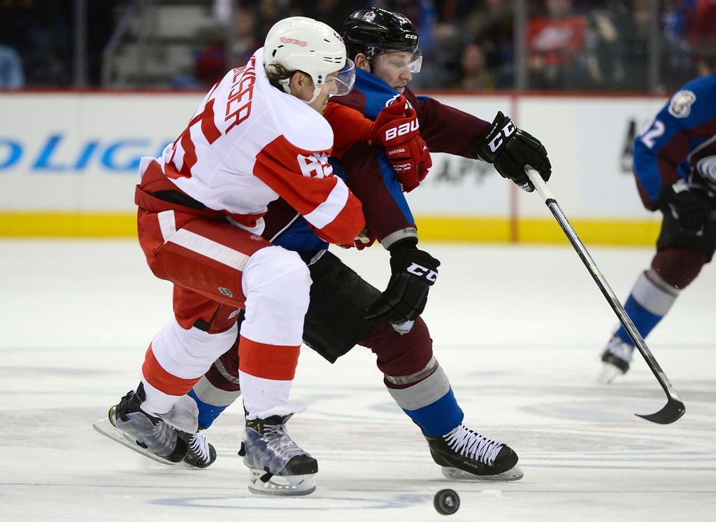 . DENVER, CO - February 5: Colorado Avalanche center Nathan MacKinnon (29) battles with Detroit Red Wings defenseman Danny DeKeyser (65) over the puck during the third period Thursday, February 5, 2015 at the Pepsi Center in Denver, Colorado. The Avalanche lost 3-0 to the Red Wings. (Photo By Brent Lewis/The Denver Post)