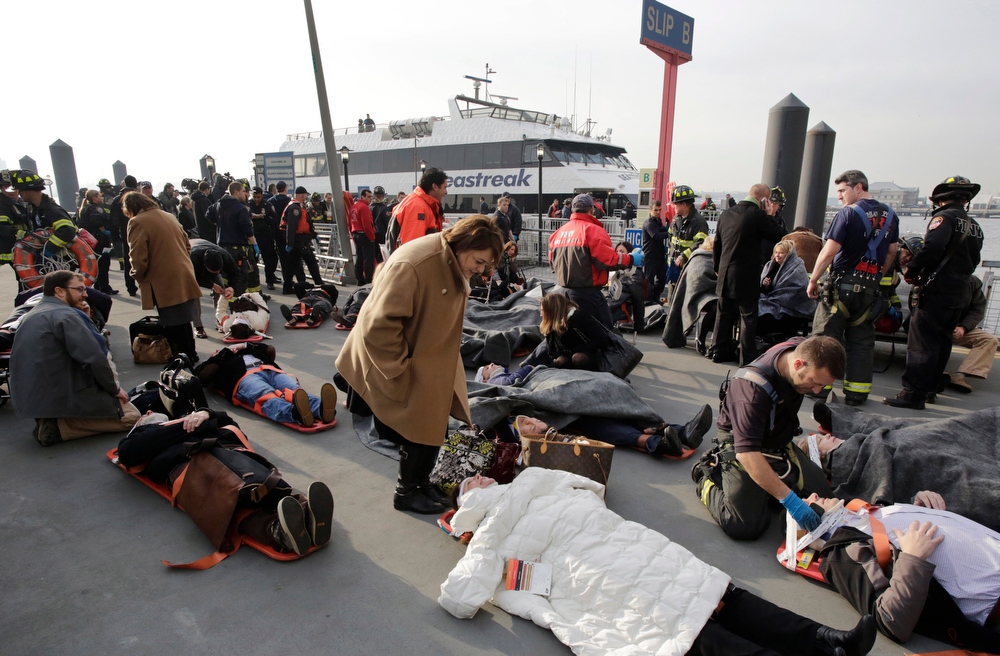 . Victims of the Seastreak Wall Street ferry accident are aided by rescue personnel, Wednesday, Jan. 9, 2013 in New York. The ferry, rear, from New Jersey made a hard landing at the dock as it pulled up to lower Manhattan during Wednesday morning rush hour, injuring as many as 50 people, at least one critically, officials said. (AP Photo/Mark Lennihan)