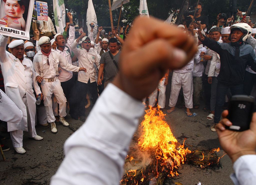 . In this Friday, Sept. 6, 2013 photo, Muslim men shout slogans as they burn the effigy of Hary Tanoesoedibjo, head of MNC media group, the local organizer of Miss World 2013, during a protest demanding the cancellation of the pageant in Jakarta, Indonesia. (AP Photo/Dita Alangkara)
