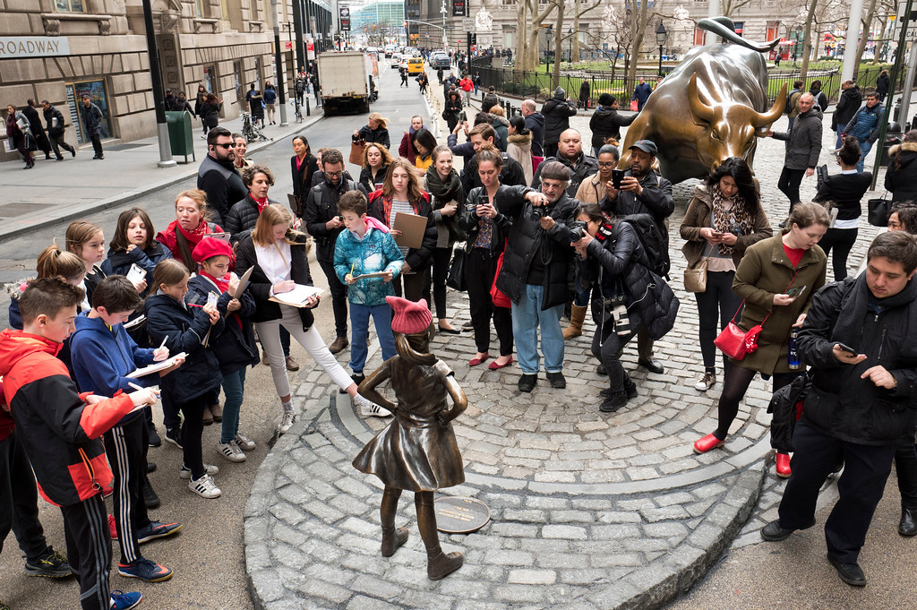 ". A crowd gathers around a statue of a fearless girl facing the Wall Street Bull, Wednesday, March 8, 2017, in New York. The statue was installed by an investment firm in honor of International Women\'s Day. An inscription at the base reads, ""Know the power of women in leadership. She makes a difference. State Street Global Advisors.\"" (AP Photo/Mark Lennihan)"