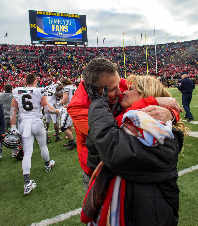 . Ohio State head coach Urban Meyer kisses his wife Shelley, right, not the Michigan Stadium field after an NCAA college football game against Michigan in Ann Arbor, Mich., Saturday, Nov. 25, 2017. Ohio State won 31-20. (AP Photo/Tony Ding)