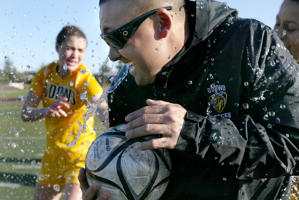 . Bishop O\'Dowd head coach Jon Nishimoto is doused with a bucket of water by her players as they celebrate their North Coast Section Division II Girls Soccer Championship game against Piedmont at Dublin High School soccer field in Dublin, Calif., on Saturday, Feb. 23, 2013. Bishop O\'Dowd won 3-2 in a series of penalty kicks. (Ray Chavez/Staff)