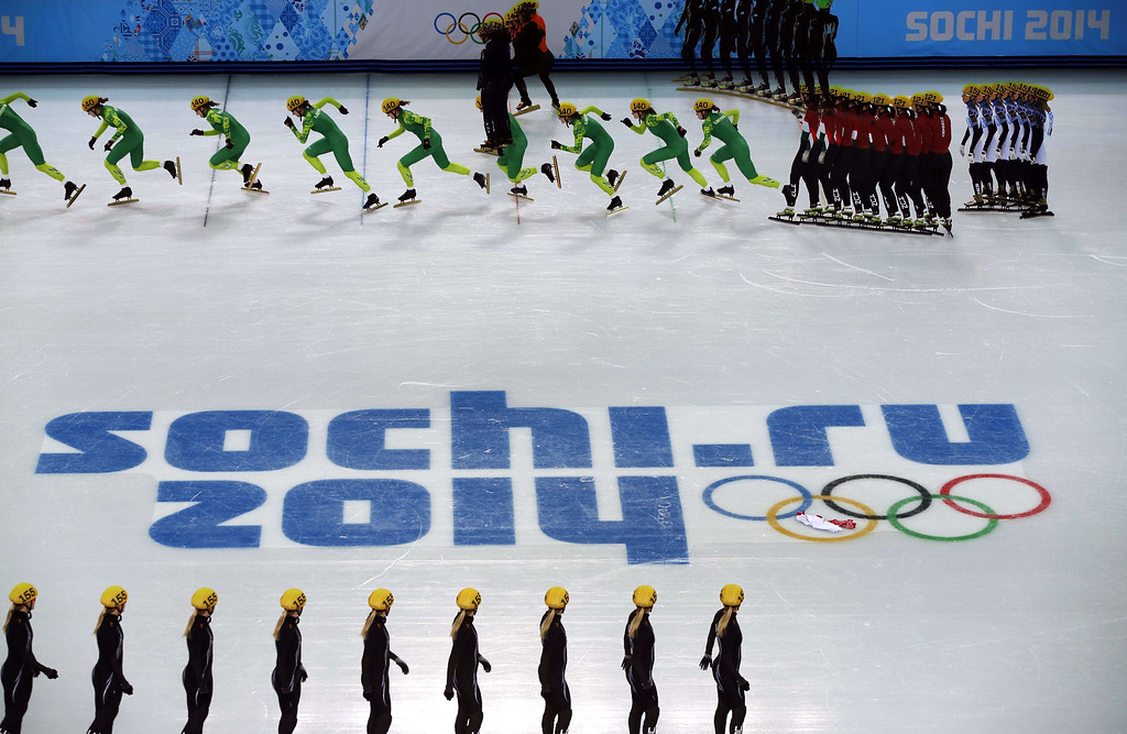 . Athletes warm up in this double exposure during the Women\'s Short Track 500 m Heats at the Iceberg Skating Palace during the Sochi Winter Olympics on February 10, 2014. ADRIAN DENNIS/AFP/Getty Images