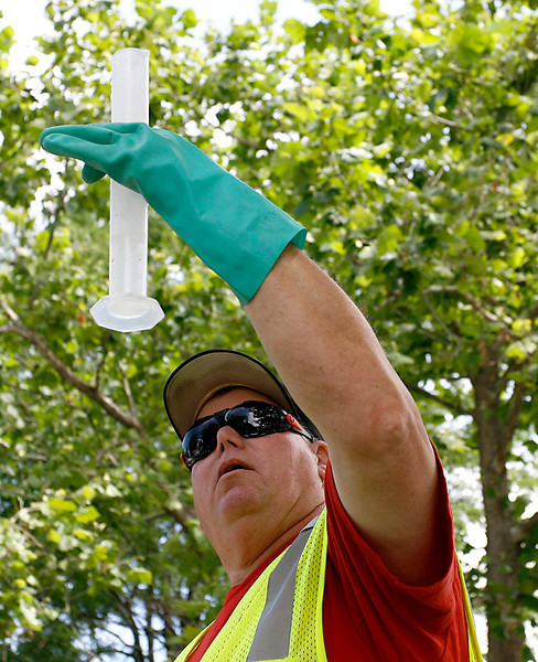 Erik Anderson/Rockford Register Star Certified Arborist Steve Farra measures a specific amount of insecticide to be used on Ash trees Thursday, June 21, 2012, on Weaver Road in Rockford.