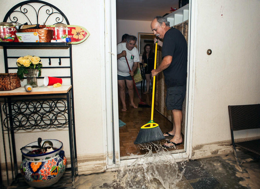 . In this Tuesday, Aug. 26, 2014 photo, residents sweep out flood water from a home in Seal Beach, Calif. after high tide and large waves caused heavy flooding.  A low-lying street in the Southern California coastal community of Seal Beach has been inundated by a surge of rising seawater brought on by Hurricane Marie spinning off Mexico\'s Pacific coast. (AP Photo/Kevin Warn)