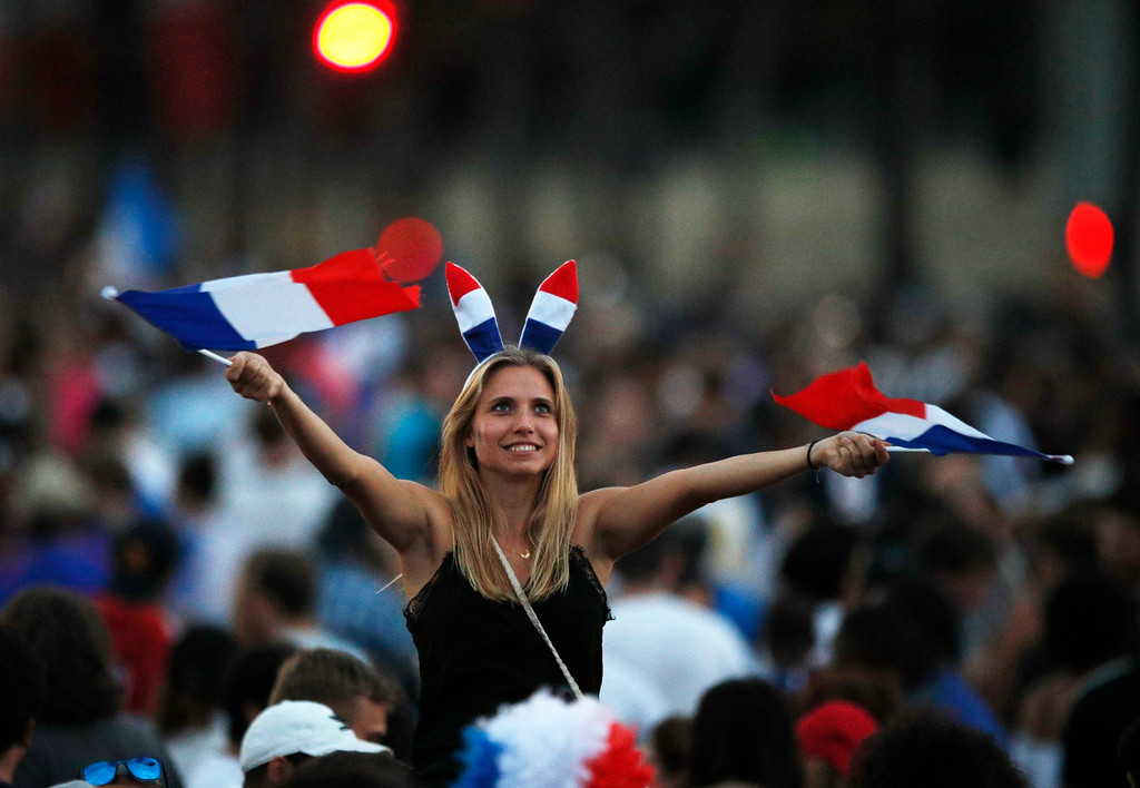 . A woman waves French flag on the Champs Elysees avenue after France won the soccer World Cup final match between France and Croatia, Sunday, July 15, 2018 in Paris. France won its second World Cup title by beating Croatia 4-2 . (AP Photo/Francois Mori)