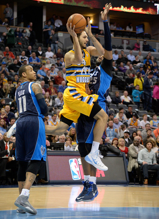 . Denver Nuggets shooting guard Evan Fournier (94) pass off  as Dallas Mavericks shooting guard Vince Carter (25) defends on the play during the first quarter March 5, 2014 at Pepsi Center. (Photo by John Leyba/The Denver Post)