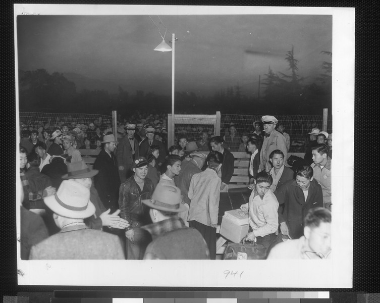 """""""Part of a 10-day evacuation program, Japanese at the Santa Anita assembly center are shown in the process of departing.  At dawn, evacuees crowd gate to check baggage, all labeled for shipment on the train with them.""""--caption on photograph"""
