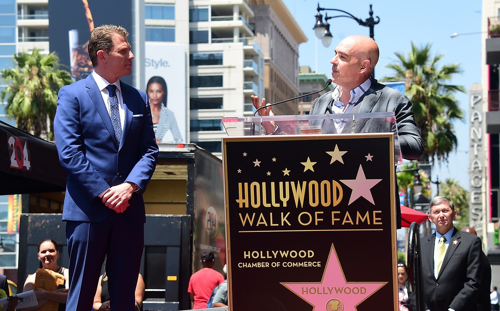 . Chef Bobby Flay listens as Chef Michael Symon speaks during Flay\'s Hollywood Walk of Fame Star ceremony on June 2, 2015, in Hollywood, California. Flay is the first television chef to be accorded the honor.         (FREDERIC J. BROWN/AFP/Getty Images)