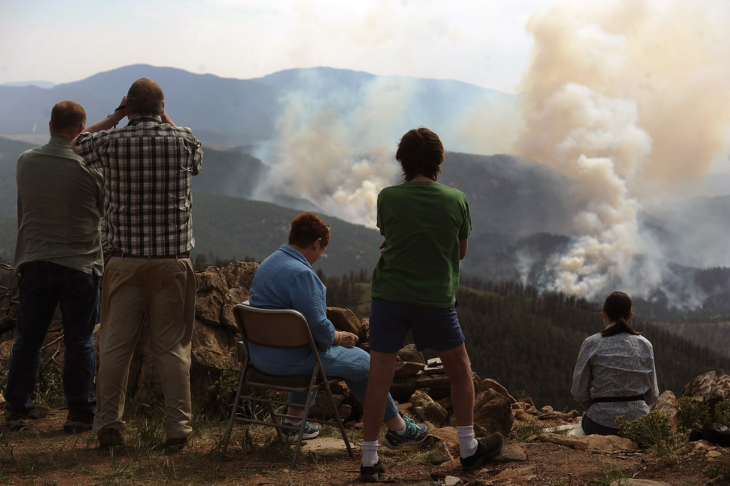 . JEFFERSON COUNTY, CO - JUNE 20:  Lower North Fork fire victims, who did not want to be identified, watch the Lime Gulch Fire across the canyon from the vantage point of where their home once stood on Eagle Vista Lane in Jefferson County, CO on June 20, 2013.  .  The Lime Gulch Fire which is burning off of Foxton Road near Conifer, CO continues to burn almost next to last year\'s Lower North Fork fire on June 20, 2013.  This area along Kuehster Road is where many homes burned in the Lower North Fork Fire in March of 2012.  Photo by Helen H. Richardson/The Denver Post)