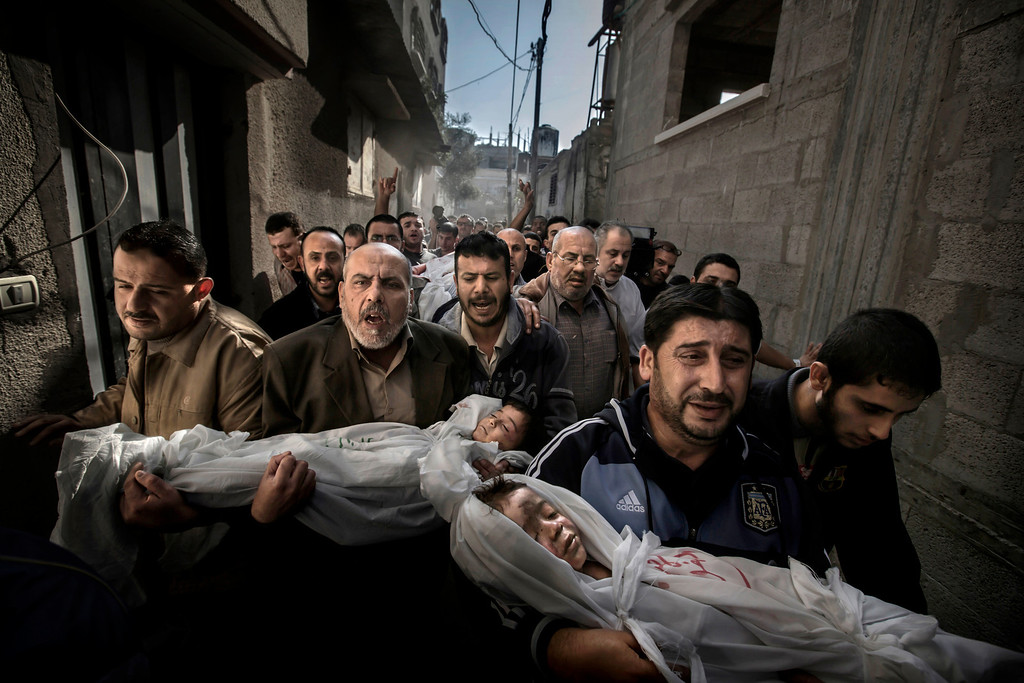 . 2013 World Press Photo of the year by Paul Hansen, Sweden, for Dagens Nyheter, shows two-year-old Suhaib Hijazi and her three-year-old brother Muhammad who were killed when their house was destroyed by an Israeli missile strike. Their father, Fouad, was also killed and their mother was put in intensive care. Fouadís brothers carry his children to the mosque for the burial ceremony as his body is carried behind on a stretcher in Gaza City, Palestinian Territories, Nov. 20, 2012. (AP Photo/Paul Hansen, Dagens Nyheter)
