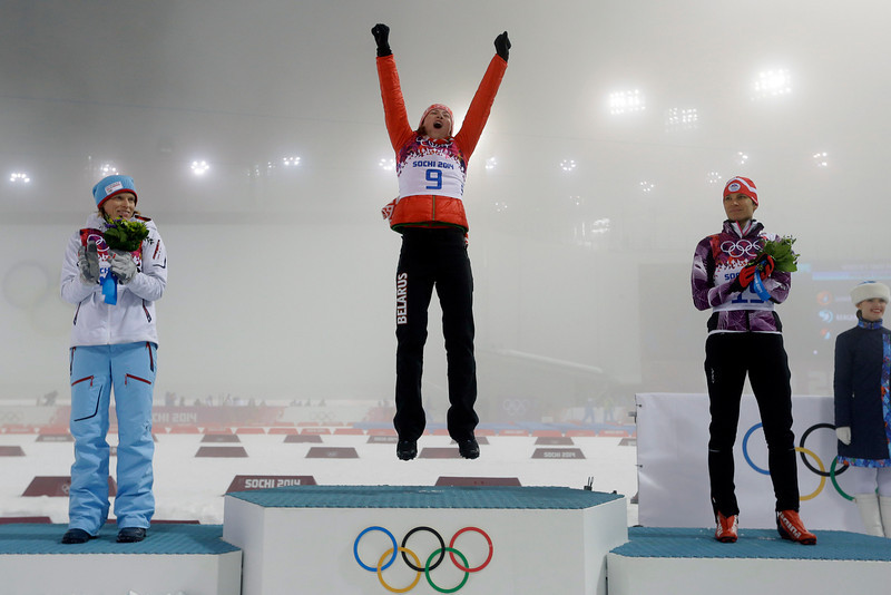 . Gold medalist Belarus\' Darya Domracheva, center, is flanked by silver medalist Norway\'s Tora Berger, left, and bronze medalist Slovenia\'s Teja Gregorin, during the flowers ceremony for the women\'s biathlon 10k pursuit, at the 2014 Winter Olympics, Tuesday, Feb. 11, 2014, in Krasnaya Polyana, Russia. (AP Photo/Kirsty Wigglesworth)