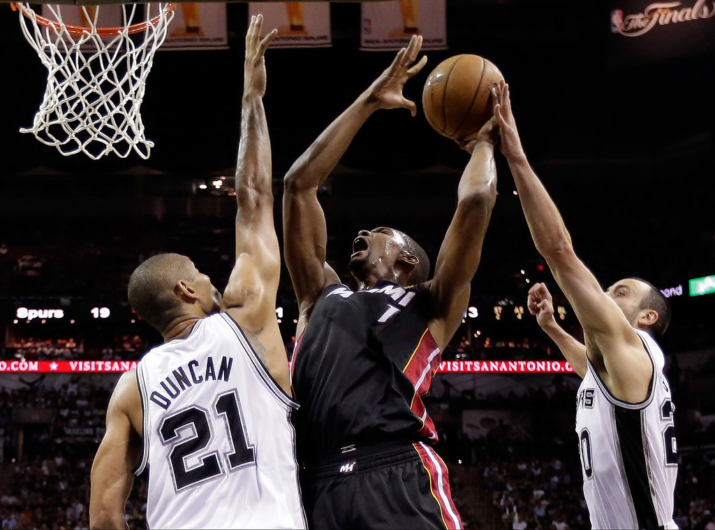 . Chris Bosh #1 of the Miami Heat goes up for a shot against Tim Duncan #21 and Manu Ginobili #20 of the San Antonio Spurs in the first half during Game Four of the 2013 NBA Finals at the AT&T Center on June 13, 2013 in San Antonio, Texas.  (Photo by Eirc Gay/Pool/Getty Images)