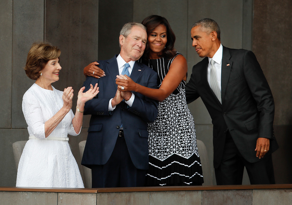 . First lady Michelle Obama, center, hugs former President George W. Bush, as President Barack Obama and former first lady Laura Bush walk on stage at the dedication ceremony of the Smithsonian Museum of African American History and Culture on the National Mall in Washington, Saturday, Sept. 24, 2016. (AP Photo/Pablo Martinez Monsivais)