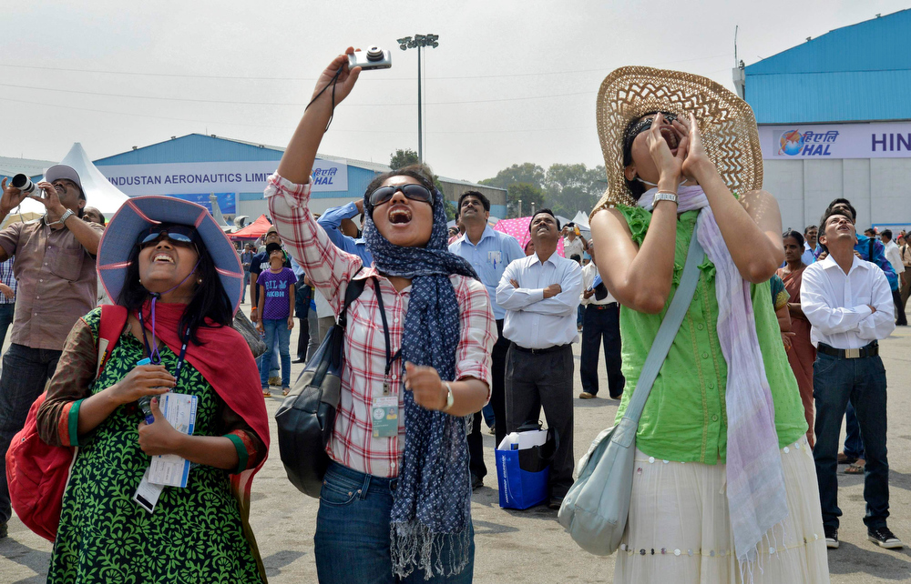 ". Visitors cheer as they watch Russian Knights, the aerobatic team of the Russian Air Force, performing in their Sukhoi Su-27 and Su-27UB fighter aircraft during ""Aero India 2013\"" on the outskirts of the southern Indian city of Bangalore February 8, 2013. REUTERS/Stringer"