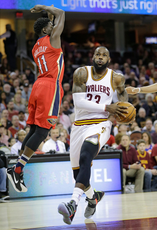 . Cleveland Cavaliers\' LeBron James (23) drives against New Orleans Pelicans\' Jrue Holiday (11) in the first half of an NBA basketball game, Monday, Jan. 2, 2017, in Cleveland. (AP Photo/Tony Dejak)