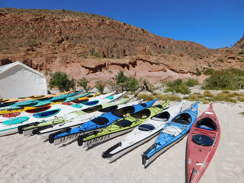 various empty kayaks on the beach