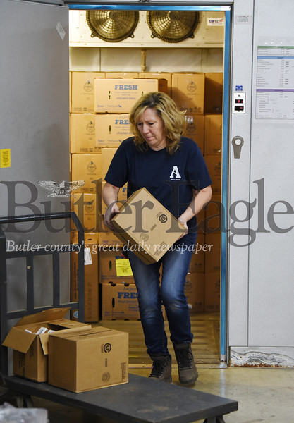 Harold Aughton/Butler Eagle: Sue Leinbnbach, a credentialing specialist for the Alliance for Non-profit Resources, removes perishable food items from the cooler for distribution to one of the county's ? number of food pantries.