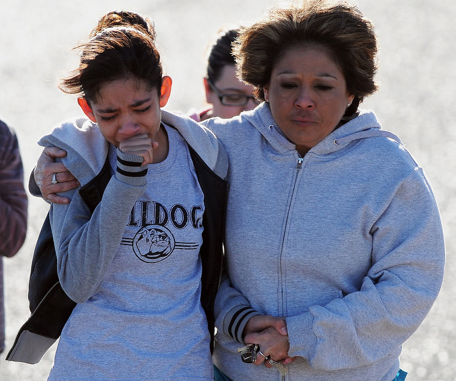 . A student, left, is hugged after being united with families following a shooting at Berrendo Middle School, Tuesday, Jan.14, 2014, in Roswell, N.M. A shooter opened fire at the middle school, injuring at least two students before being taken into custody. Roswell police said the school was placed on lockdown, and the suspected shooter was arrested. (AP Photo/Roswell Daily Record, Mark Wilson)