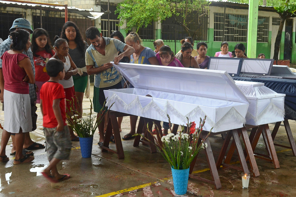 . Friends and relatives stand next to caskets containing the remains of members of the Gallegos family after a landslide buried a home on the outskirts of the Pacific resort city of Acapulco, Mexico, Monday, Sept. 16, 2013. Twin storms, Manuel and Ingrid, left scenes of havoc on both of Mexico\'s coasts. (AP Photo/Bernandino Hernandez)