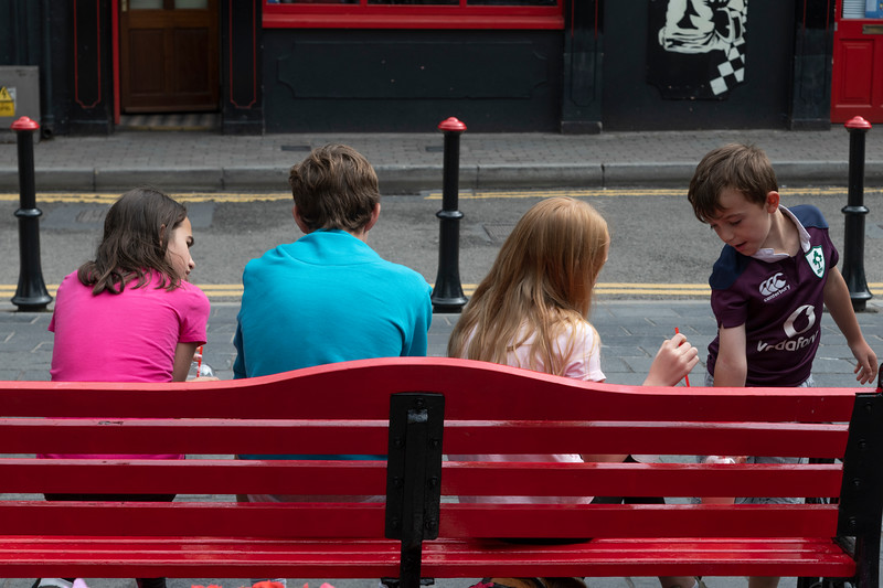 Siblings sitting together on bench, Kinsale, County Cork, Ireland