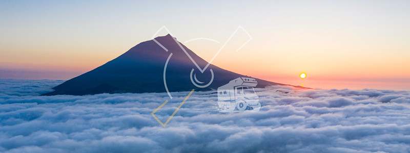 Aerial image with magical sunset over a low cloud layer covering Pico Island, with Ponta do Pico (Mount Pico), the highest mountain of Portugal coming through the clouds and a smaller volcano crater in the foreground, Azores
