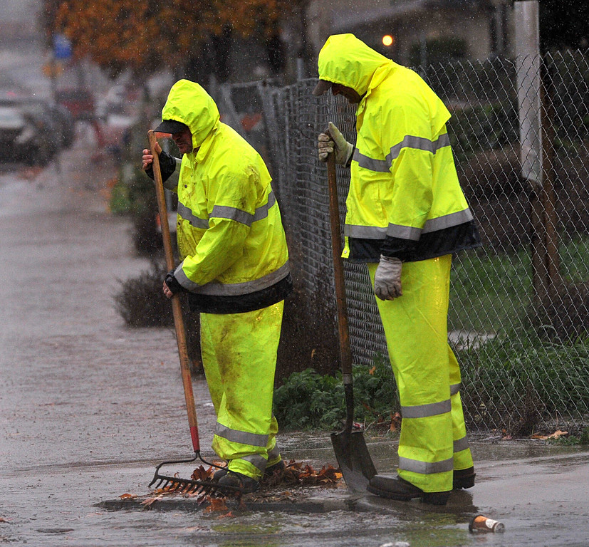 . City workers rake away leaves blocking a drain at the corner of L Street and Sycamore Drive as heavy rains and winds cause problems in Antioch, Calif., on Thursday, Dec. 11, 2014.  (Dan Rosenstrauch/Bay Area News Group)