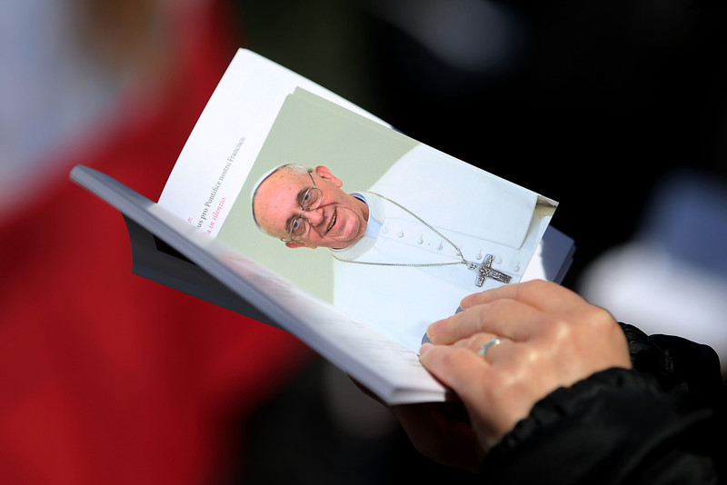 . A wellwisher holds an image of Pope Francis during the Inauguration Mass for Pope Francis in St Peter\'s Square on March 19, 2013 in Vatican City, Vatican. The mass is being held in front of an expected crowd of up to one million pilgrims and faithful who have filled the square and the surrounding streets to see the former Cardinal of Buenos Aires officially take up his role as pontiff. Pope Francis� inauguration takes place in front of Cardinals and spiritual leaders as well as heads of state from around the world.  (Photo by Joe Raedle/Getty Images)