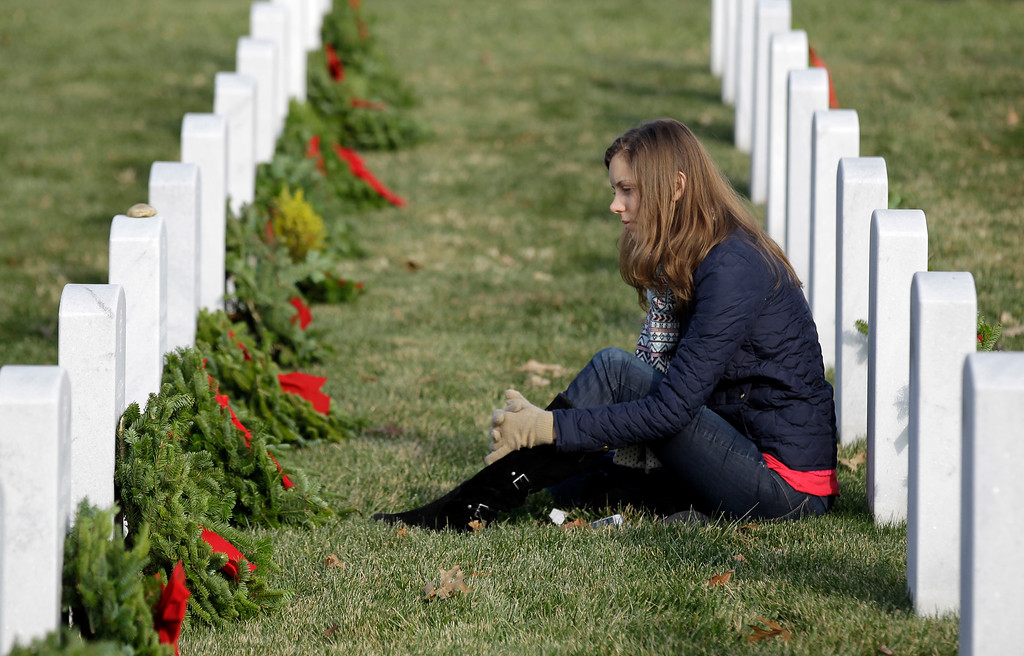 . Lianna Bennett sits at the headstone of her grandfather U.S. Army Col. William W. Etchemendy during Wreaths Across America\'s 150th anniversary, Saturday, Dec. 13, 2014, at Arlington National Cemetery in Arlington, Va. (AP Photo/Luis M. Alvarez)