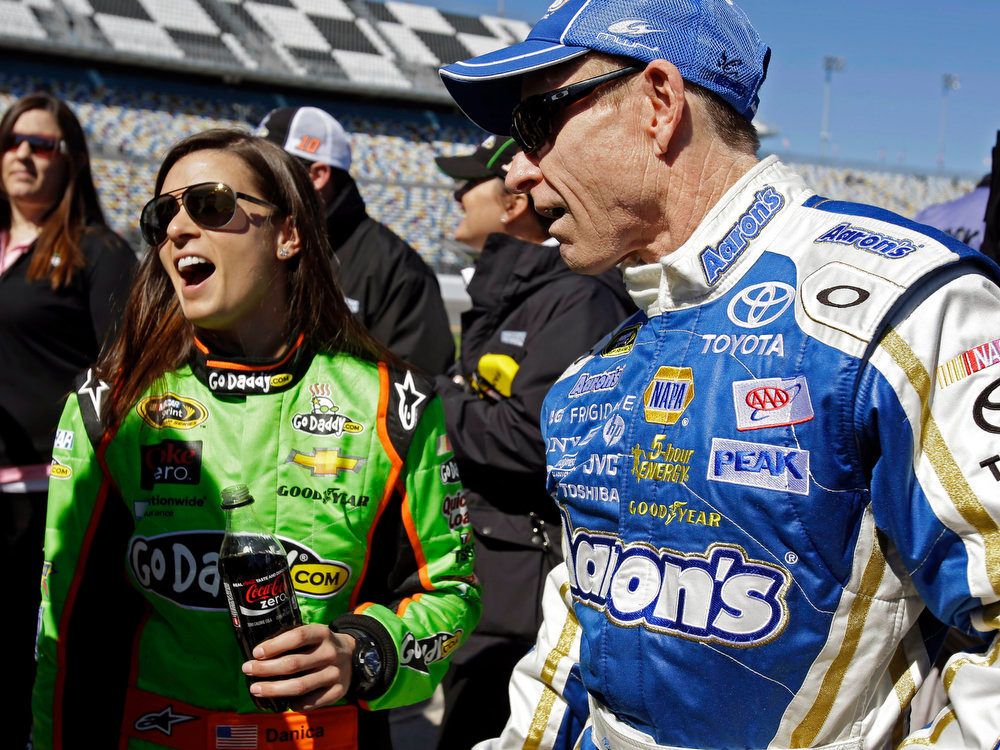 Description of . Mark Martin, right, and Danica Patrick laugh on pit road after their qualifying runs for the NASCAR Daytona 500 Sprint Cup Series auto race at Daytona International Speedway, Sunday, Feb. 17, 2013, in Daytona Beach, Fla. Patrick won the pole, becoming the first woman to secure the top spot for any Sprint Cup race. (AP Photo/John Raoux)