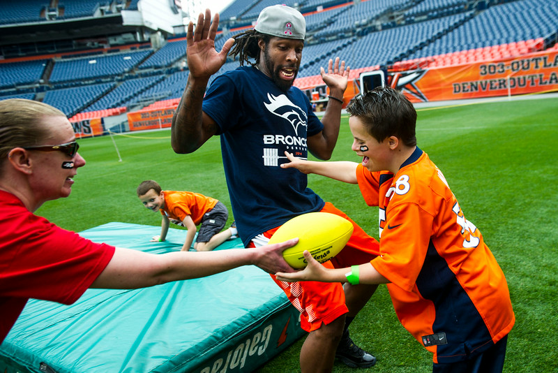 . Andrew Goodspeed, 14, pushes David Bruton #30 of the Denver Broncos as he gets a hand off from volunteer Jamie McWhirt during the National Sports Center for the Disabled\'s Denver Broncos Ability Clinic at Sports Authority Field on Tuesday, July 08, 2014 in Denver, CO. More than 200 children and adults with disabilities will learn skill development and interact with players from The Denver Broncos.  (Photo by Kent Nishimura/The Denver Post)