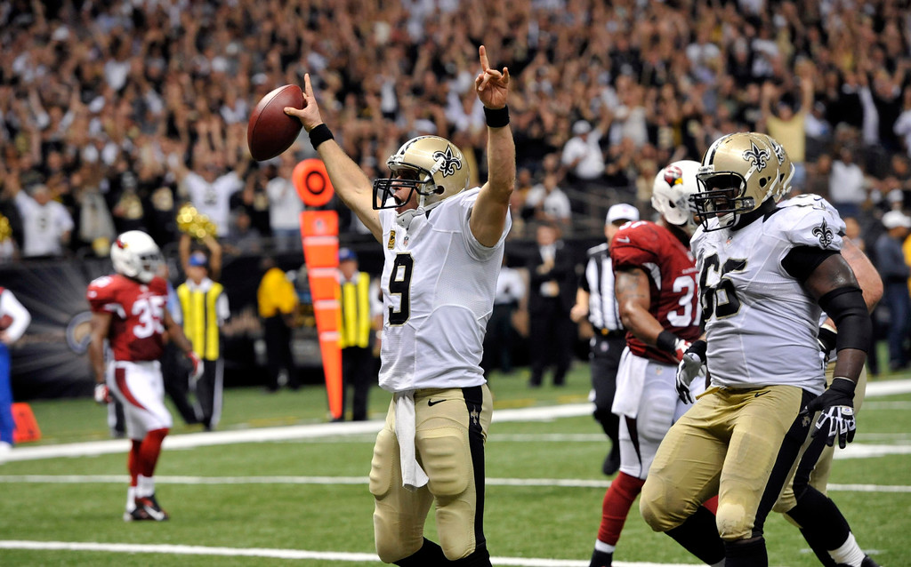 . New Orleans Saints quarterback Drew Brees (9) celebrates after rushing for a touchdown in the second half of an NFL football game against the Arizona Cardinals in New Orleans, Sunday, Sept. 22, 2013. (AP Photo/Bill Feig)