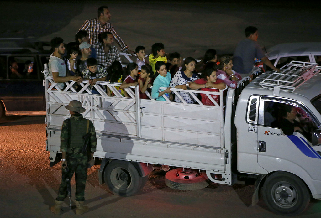 . Fleeing Iraqi citizens from Mosul and other northern towns sit in a truck as they cross to secure areas at a Kurdish checkpoint, in the Khazer area between the Iraqi city of Mosul and the Kurdish city of Irbil, northern Iraq, Wednesday, June 25, 2014.  (AP Photo/Hussein Malla)