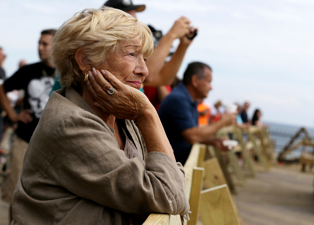 . A woman looks on as people gather on the Seaside Park boardwalk to look at the destruction left behind after a massive fire that started a day earlier, Friday, Sept. 13, 2013, in Seaside Park, N.J.  (AP Photo/Julio Cortez)
