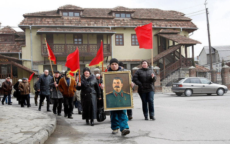 . Georgians carry a portrait of former Soviet dictator Joseph Stalin and red flags during a ceremony marking the 60th anniversary of Stalin\'s death in his home town of Gori, 50 miles west of the Georgian capital Tbilisi, on Tuesday, March 5, 2013. Georgian communists, who flocked to Stalin\'s hometown of Gori for the anniversary, hope that the government of Prime Minister Bidzina Ivanishvili, whose bloc defeated Saakashvili\'s party in parliamentary elections last fall, will restore the Stalin monument torn down on Georgian President Mikhail Saakashvili\'s orders. (AP Photo/Shakh  Aivazov)