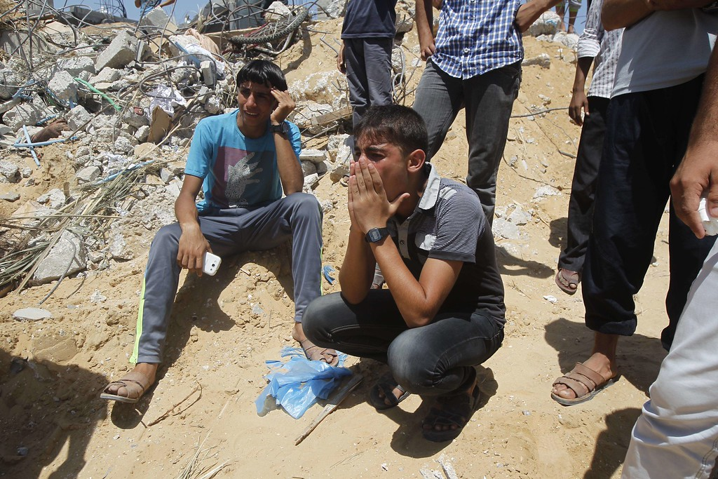 . Palestinian youths weep as they watch rescue workers on July 30, 2014 removing the body of a dead child from under the rubble of the Duheir family home which was destroyed in an Israeli air strike the previous day in Rafah in the southern Gaza Strip.  At least 54 people died in Israeli strikes across Gaza on July 30, including 16 killed when shells hit a UN school, sending the Palestinian toll from 23 days of fighting to more than 1,280. AFP PHOTO/ SAID  KHATIB/AFP/Getty Images