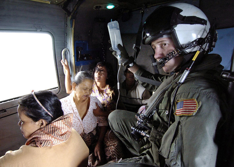 . In this picture released by the U.S. Navy, Air crewman Matt Gardner, of Phoenix, Az., assigned to the Saberhawks of Helicopter Anti-Submarine Squadron Light Four Seven, holds the IV bottle of an ill Indonesian woman during a humanitarian aid mission to Aceh, Sumatra, Indonesia Tuesday Jan. 4, 2005. Helicopters and aircraft assigned to Carrier Air Wing Two (CVW-2) and Sailors from Lincoln are conducting humanitarian operations in the wake of the Tsunami that struck South East Asia. The Abraham Lincoln Carrier Strike Group is currently operating in the Indian Ocean off the waters of Indonesia and Thailand.  (AP Photo/U.S. Navy,Tyler J. Clements/HO)
